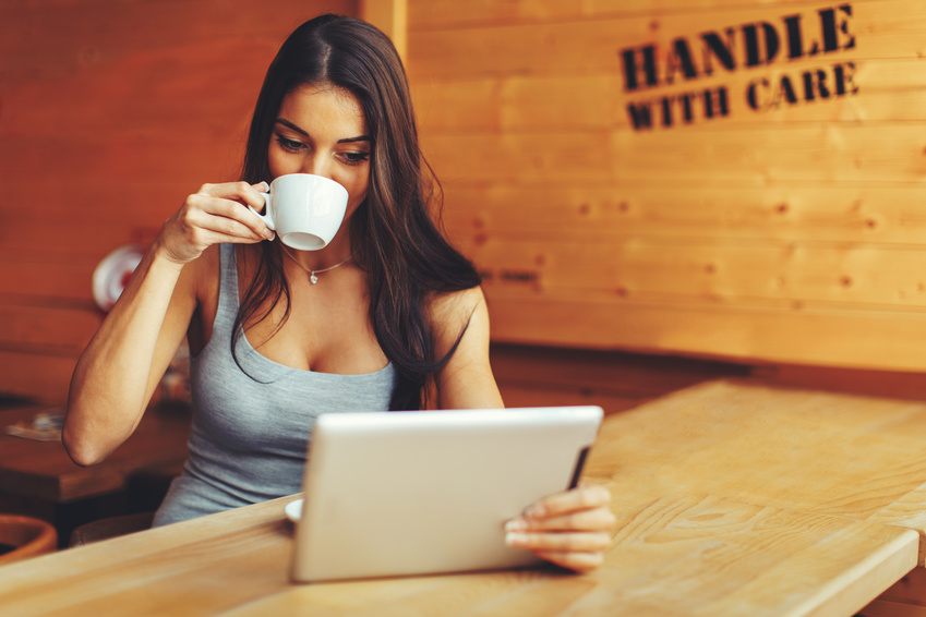 Young woman drinking coffee and using digital tablet in cafe